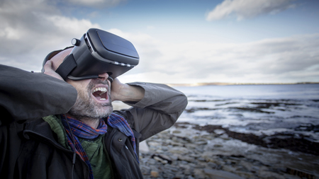 A front-view shot of a mature caucasian man wearing a virtual reality headset while standing on a beach in the United Kingdom, he has his arms raised is expressing anger.