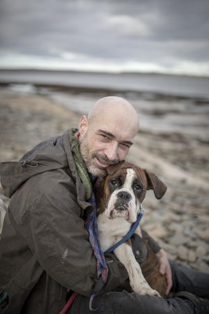 A front-view shot of a mature caucasian man sitting on a beach with his brown and white boxer dog, they are embracing eachother on the cold day in the United Kingdom.