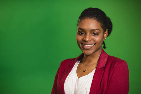 A front-view portrait shot of a young africian woman standing in front of a green screen, she is smiling and looking at the camera. 写真素材 - 124934407
