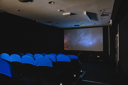 A rear view shot of an empty movie theater, blue seats sit in a row infront of the projection screen.