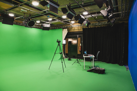 A wide-angle shot of a film studio, a green screen surrounds the room interior, a tripod stands in the middle of the room with a camera ready to film and a desk sits at the back of the room with a laptop and equipment.