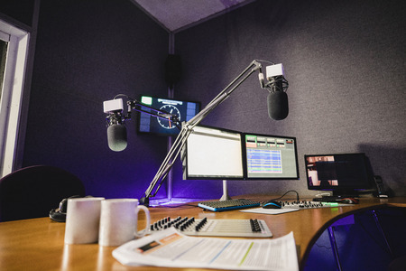 A front view shot of a radio station studio interior, a large desk is in the middle of the room, recording equipment and computers can be seen on the desk. Imagens