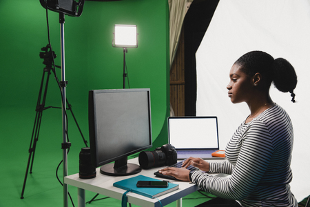 A close-up side-view shot of a young african woman working at her desk in a film studio, a computer, laptop, smart phone and camera can be seen on the desk, the young woman is showing her dedication by working late.