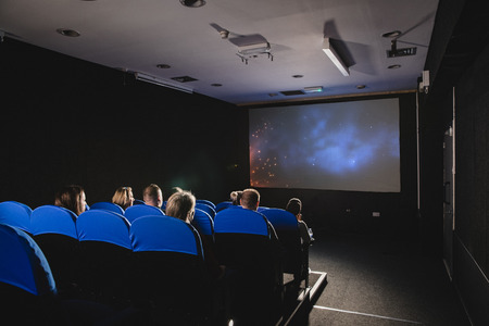 A rear view shot of a movie theater, unrecognizable people can be seen sitting together in blue seats in a row infront of the projection screen.