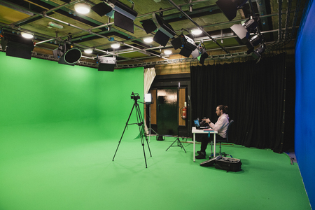 A wide-angle shot of a caucasian man working at his desk in a film studio, a green screen surrounds the room interior, ready for use. Фото со стока