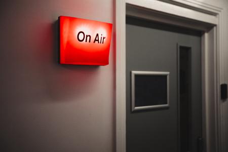 A close-up shot of a red on air sign on a wall in a recording studio, next to a doorway. Archivio Fotografico