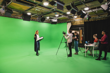 A wide-angle shot of a multi-ethnic group of people working in a film studio, a mature caucasian woman can be seen presenting in front of a green screen. Banco de Imagens