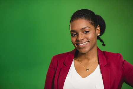 A front-view portrait shot of a young africian woman standing in front of a green screen, she is smiling and looking at the camera. Stock Photo