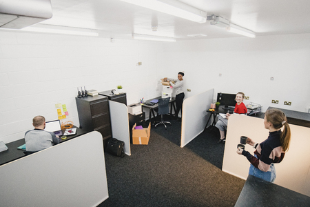 A wide view shot of a small multi-ethnic group of people working in an office, they can be seen discussing work with their colleagues.