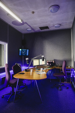 A front view shot of a radio station studio interior, a large desk is in the middle of the room, recording equipment and computers can be seen on the desk. Фото со стока