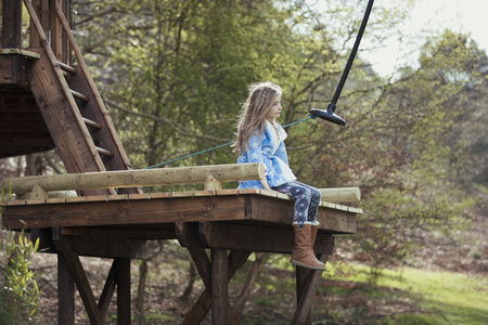 Little girl is sitting peacefully on the platform of a monkey swing in her garden.