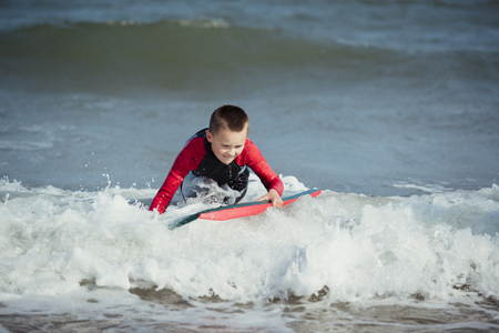 Little boy is trying to stand up on his surf board in the sea.