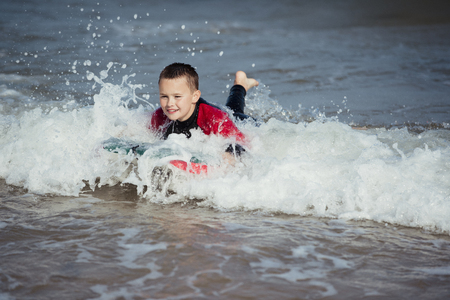 Little boy playing in the surf with a bodyboard. Stock Photo