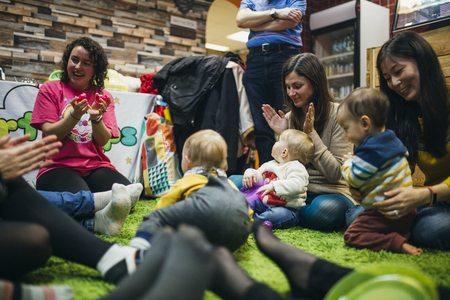 Mothers and their baby children are in a sensory play group. They are singing and dancing together in a circle on the floor. Stock Photo
