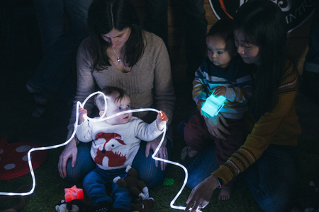 Mother and baby sensory play group are using LED lighting and toys for developmental play.