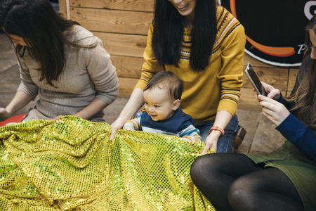 Close up shot of a little boy in a mother and baby sensory play group. They are playing with a textured fabric sheet. 写真素材