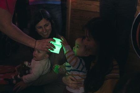 Close up shot of a baby boy having fun in a sensory group with illuminated toys.