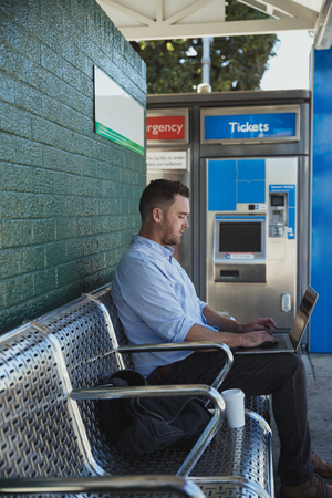 A side-view shot of a mid-adult caucasian businessman working on his laptop while he is sitting waiting for the train at a railroad station platform. Stock Photo