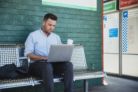 A side-view shot of a mid-adult caucasian businessman working on his laptop while he is sitting waiting for the train at a railroad station platform, he is holding a cup of coffee.