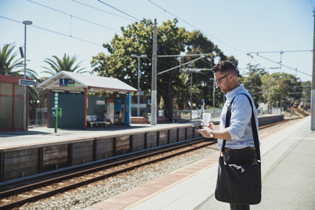 A side-view shot of a mid-adult caucasian businessman waiting at a railroad station platform with a cup of coffee in his hand, he is catching the train.