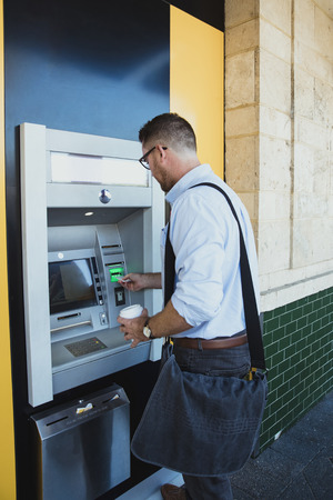 A rear-view shot of a caucasian businessman using an ATM machine in Perth Australia, he is inserting his credit card to withdraw money.