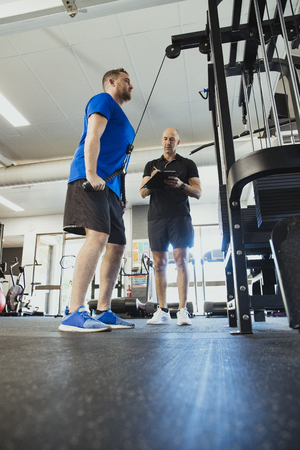A low-down shot of a mid-adult caucasian man training in the gym, he is strengthening his triceps. A fitness instructor can be seen standing by the mans side motivating him. Reklamní fotografie