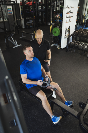 A  high-angle view of a mid-adult caucasian man training in the gym, he is using a rowing machine. A fitness instructor can be seen standing by the mans side showing him a technique.