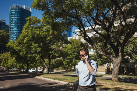 A side-view shot of a mid-adult caucasian businessman walking to work on a sunny day in Perth, Australia. He is holding a laptop and he is talking on his smart phone.