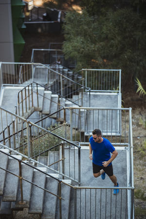 A high angle view of a caucasian mid-adult man running up a narrow staircase in the city on a hot summers day in Perth, Australia. Reklamní fotografie