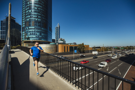 A front-view shot of a caucasian mid-adult man jogging in the city on a hot summers day in Perth, Australia.