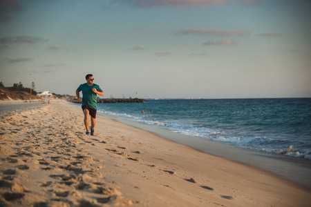 A front-view shot of a caucasian mid-adult man jogging across the beach on a hot summers day in Perth, Australia.