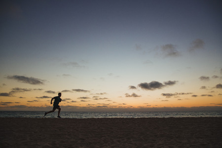 A side-view shot of a caucasian mid-adult man jogging across the beach in Perth, Australia. The sun is setting behind him.