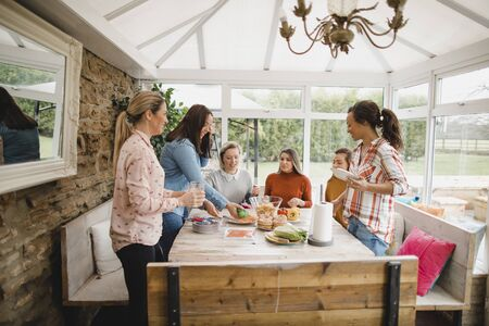 Small group of female friends preparing a healthy lunch inside of a conservatory on a weekend away.
