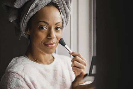 Mid adult mixed race woman applying make-up during her daily morning routine. She is looking at the camera and smiling.