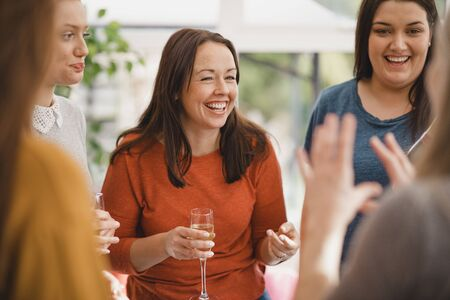 Small group of female friends celebrating at a house party. They are enjoying a glass of champagne, laughing and smiling.