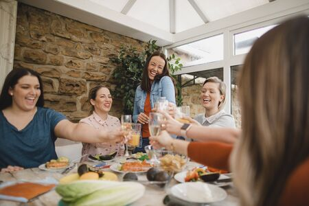 Small group of female friends preparing a healthy lunch inside of a conservatory on a weekend away. They are making a celebratory