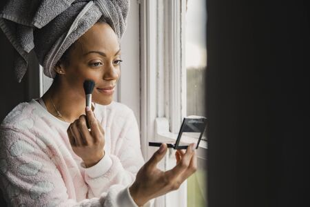 Mid adult mixed race woman applying make-up during her daily morning routine. Reklamní fotografie