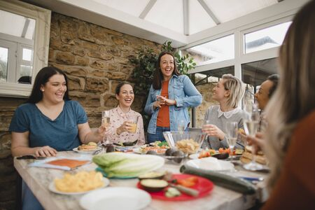 Small group of female friends preparing a healthy lunch inside of a conservatory on a weekend away. 写真素材 - 124813621