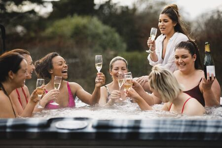 Small group of female friends socialising and relaxing in the hot tub on a weekend away. They are celebrating with a glass of champagne. Reklamní fotografie