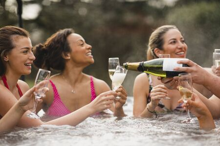 Small group of female friends socialising and relaxing in the hot tub on a weekend away. They are celebrating with a glass of champagne. 写真素材 - 124815031