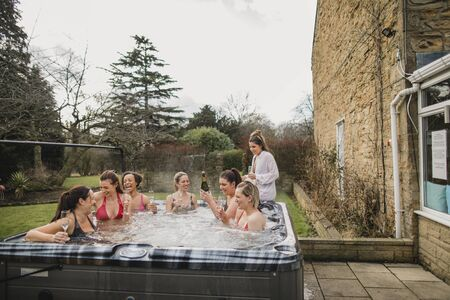 Small group of female friends socialising and relaxing in the hot tub on a weekend away. They are celebrating with a glass of champagne. 写真素材 - 124815104