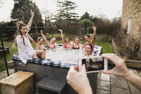 Small group of female friends relaxing and celebrating in a hot tub. They are all looking towards their friend who is taking a group photo of them. 写真素材 - 124815131