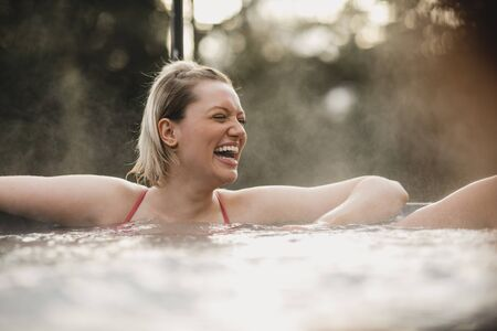 Mid adult woman relaxing in a hot tub with her friends.