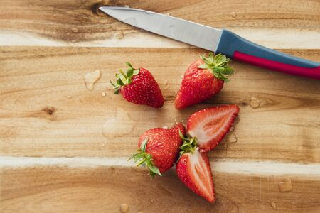 High angle view of strawberries, sliced, on a wooden chopping board next to a knife. Reklamní fotografie