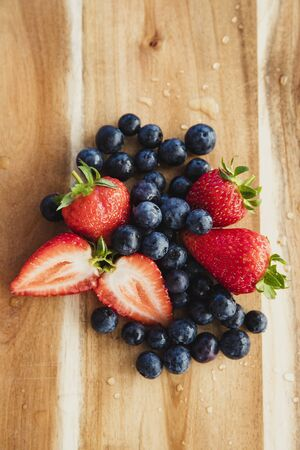 High angle view of blueberries and strawberries, sliced, on a wooden chopping board.