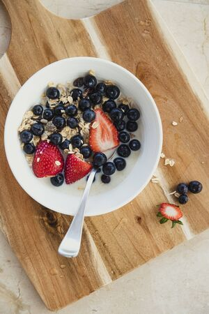 HIgh angle view of a fresh healthy breakfast. There is fresh fruit, oats and milk in a bowl with a spoon. The bowl is placed on a wooden chopping board. Reklamní fotografie