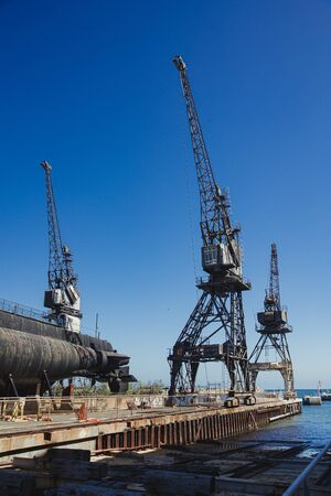 Abandoned cranes at the docks in Perth, Australia. There is a submarine on stilts where it would be repaired.