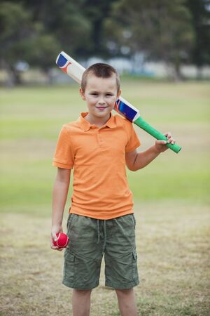 A portrait shot of a young caucasian boy wearing casual clothing, he is holding a cricket bat and ball and he is looking at the camera.