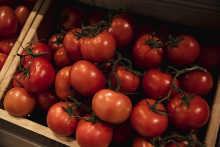 A close-up shot of an abundance of fresh Red Tomatoes on display at a market stall.