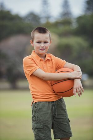 A portrait shot of a young caucasian boy wearing casual clothing, he is holding a basketball and looking at the camera.
